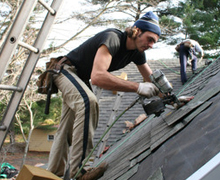 Roofer shingling a roof